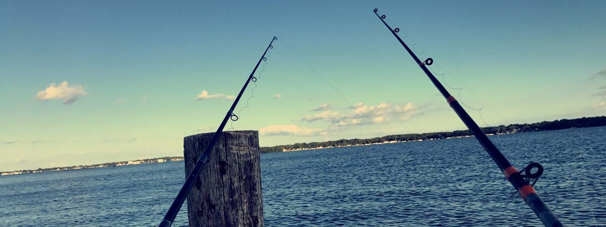 Fishing rods on pier in sunset